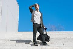 Kerl im Freizeitkleidungsstand auf Treppe auf blauem Himmel, Mode Mann mit Tasche, Smartphone auf Schritten auf sonnigem im Freie Lizenzfreie Stockfotos