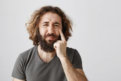 Kerl ist düster, dass er altert Porträt des Umkippenjammernden Ostmannes mit Bart und dem gelockten Haar zeigend auf Falte stockbild