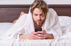 Kerl liegt im Bett Netter junger Mann wacht auf, nachdem er morgens geschlafen hat Männer im Bett stockfoto