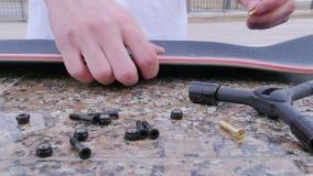 Kerl macht Bolzenlöcher im Skateboard stock video footage