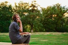 Kerl mit Buch sprechend am Telefon im Park Lizenzfreie Stockfotografie
