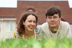 Kerl mit dem Mädchen, das auf Rasen vor neuem Haus liegt Stockfotografie