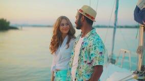 Kerl mit dem Mädchen trifft einen Sonnenuntergang auf der Yacht stock video