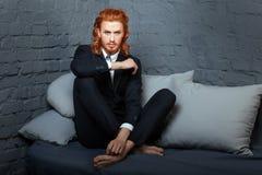 Kerl mit dem roten Haar und dem Bart, sitzend auf dem Sofa Lizenzfreie Stockfotos