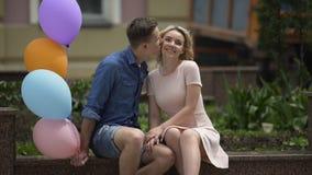 Kerl mit den Luftballonen, die seine Freundin, sie auf der Backe küssend umarmen und streicheln stock footage