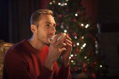 Kerl mit einem Becher Tee am Weihnachtsbaum Lizenzfreie Stockfotos