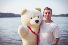 Kerl mit einem großen Teddybären lizenzfreie stockbilder