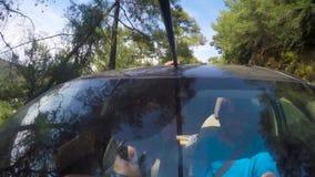 Kerl mit einem Mädchenreiten im Auto im Sommer