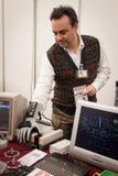 Kerl mit elektronischem Handschuh am Roboter und Hersteller stellen dar Stockfotos