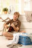 Kerl mit Gitarre und Wäscherei Lizenzfreies Stockfoto