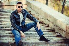 Kerl mit tragender Lederjacke und Sonnenbrille der Haltung heraus Lizenzfreies Stockfoto