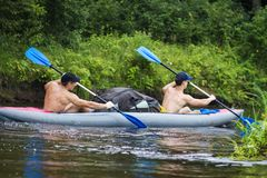 Kerl mit zwei junger Sport in den Rudern eines Bootsrudersports auf dem Wasser Kayak fahren entlang dem Fluss in der Sommersaison stockbild