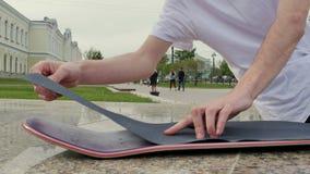 Kerl richtet die raue Oberfläche aus und setzt sie auf das Skateboard stock video