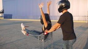 Kerl rollt attraktive junge Frau in der Laufkatze in den Motorradsturzhelmen bei Sonnenuntergang Langsame Bewegung Lustige Paare stock video