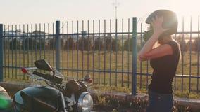 Kerl rollt attraktive junge Frau in der Laufkatze in den Motorradsturzhelmen bei Sonnenuntergang Langsame Bewegung Lustige Paare stock footage
