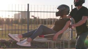 Kerl rollt attraktive junge Frau in der Laufkatze in den Motorradsturzhelmen bei Sonnenuntergang Langsame Bewegung Lustige Paare stock video footage