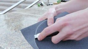 Kerl schneidet die Oberfläche des Skateboards mit einem Messer stock footage