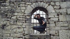 Kerl sitzt auf dem Fenster hinter den Stangen in der Festung und versucht, sie zu verlassen stock video footage