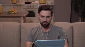 Kerl sitzt auf Sofa und betrachtet Tablette Er hat Kopfhörer in den Ohren Bärtiger Mann versucht zu sprechen Er hat Video stock video