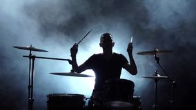 Kerl spielt die Musik auf der Trommel Schwarzer rauchiger Hintergrund Schattenbilder Weicher Fokus Langsame Bewegung stock footage