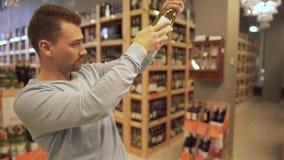 Kerl spinnt eine Flasche Wein und wertet seine Qualität an einer Weinhandlung aus stock video footage