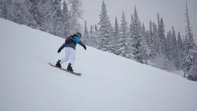 Kerl steigt vom Berg auf Snowboard im slowmo ab stock footage