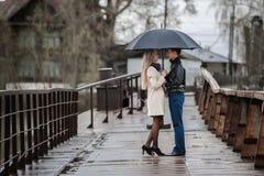 Kerl und das Mädchen unter einem Regenschirm auf der Brücke Stockfoto