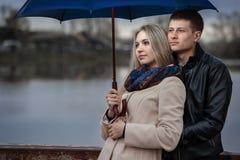 Kerl und das Mädchen unter einem Regenschirm auf der Brücke Stockfotos