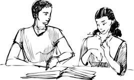 Kerl und ein Mädchen, das ein Buch am Tisch liest Lizenzfreies Stockbild