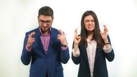 Kerl und ein Mädchen in den Anzügen kreuzten ihre Finger, die herzlichst für den erfolgreichen Projektanfang wünschen Lizenzfreie Stockfotos