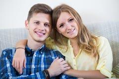 Kerl und hübsches Mädchen, die zuhause auf Sofa streicheln Stockfoto