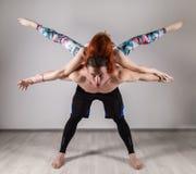 Kerl und junge Frau, die Stärkeübungen in Yoga assanes tun Acroyoga-Konzept Stockfotos