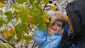 Kerl und Kinderspiele mit einem schneebedeckten Baumast Lizenzfreies Stockbild