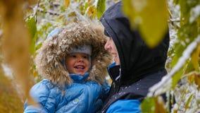 Kerl und Kinderspiele mit einem schneebedeckten Baumast Stockfotografie