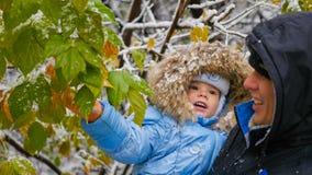 Kerl und Kinderspiele mit einem schneebedeckten Baumast Lizenzfreie Stockbilder