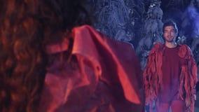 Kerl und Mädchen in den roten Kostümen stehen und starren entlang einander im Nachtwald an stock footage