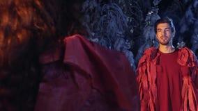 Kerl und Mädchen, die rote Kleidung entlang, einander im Nachtwald zu stehen tragen und anzustarren stock footage