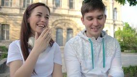 Kerl und Mädchen, Studenten, sitzen im Park, schießen das Video im Telefon und im Lachen stock video footage