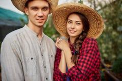 Kerl- und Mädchengärtner in Strohhüte stehen zusammen im Garten an einem sonnigen Tag stockbild