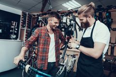 Kerl und Schlosser Fixes Bicycle im Sport-Speicher stockfoto