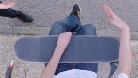 Kerl verkratzt ein Skateboard und grüßt einen Freund stock video