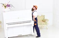 Kerl von beweglichem altem Klavier des Verkehrsunternehmens allein Müder Kerl, der schweres Material anhebt stockbild