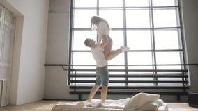 Kerl züchtet seine Freundin in seinen Armen über ihm auf dem Bett Junge flirtende Paare stock video