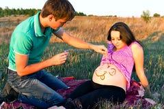 Kerl zeichnet ein Gesicht auf einem Magen der schwangeren Frau Stockfotos