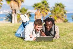 Kerle, die Computer im Gras teilen Stockfotos