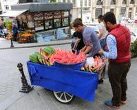 Kerle, die Wassermelone schneiden, um an ihrem Verkäufer an Galata-Bezirk von Istanbul zu verkaufen Lizenzfreie Stockfotos