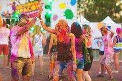 Kerle mit einem Mädchen feiern holi Festival stockbilder