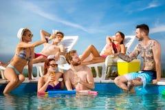 Kerle und Mädchen erneuert auf Swimmingpool mit Getränken stockbild