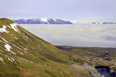 Kerlingarfjoll mountainside. Red mountainside with patches of snow and vegetation above a sea of clouds with glacier capped blue mountain range in the distance royalty free stock photos