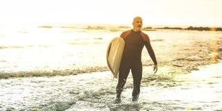 Kerlsurfer, der mit Surfbrett bei Sonnenuntergang in Teneriffa geht - Ausbildungspraktiker des langen Brettes der Brandung in der lizenzfreie stockfotografie